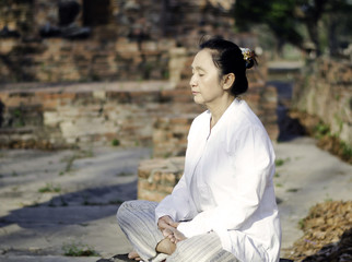 Asian woman meditating in ancient buddhist temple