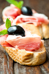 Sandwiches with prosciutto olive on wooden cutting board vertica