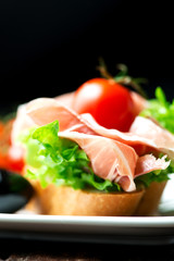 Sandwiches with prosciutto on plate