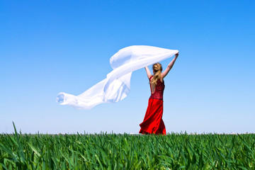 Girl with billowing white cloth runs on green field
