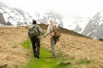 Couple of hikers with backpacks walking