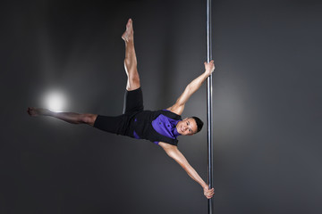 Pole dance man over black background with flashes