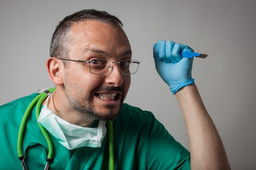 Funny crazy doctor holding a surgical knife