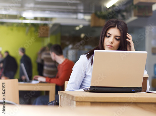 Pensive young beautiful businesswoman sitting at desk