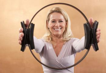 Frau hält Pilatesring
