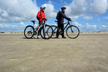 Paar mit dem Fahrrad am Sandstrand