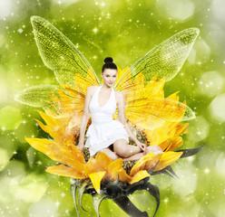 Beautiful brunette woman as summer fairy on sunflower