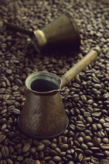 Two vintage coffee cezve over coffee bean background