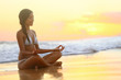 Relaxing - Yoga woman meditating at beach sunset