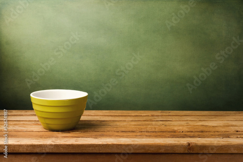 Empty green bowl on wooden table over grunge green background