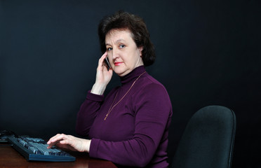 The aged woman in front of a monitor talking on cell phones