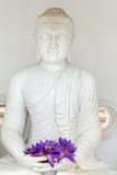 Buddha image statue with fresh flowers
