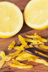 Peeling lemons on wooden table.