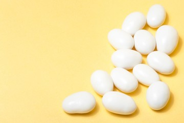 white jordan almonds on yellow background