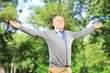 Happy gentleman spreading his arms in a park
