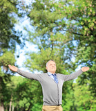 Happy gentleman spreading his arms and looking upwards in a park