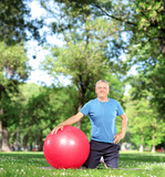 Mature male with an exercise ball in a park