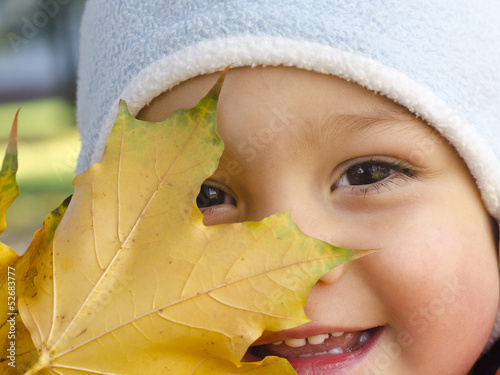Portrait of a child with autumn or fall leave.