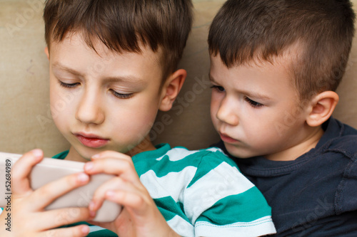 Preschool boys playing on smartphone