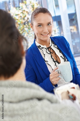 Pretty businesswoman chatting to coworker