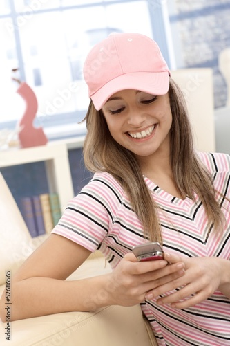 Sporty girl using mobile phone smiling