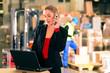 Frau mit Telefon in Lagerhalle einer Spedition