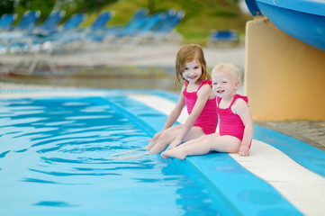 Two sisters sitting by a swimming pool