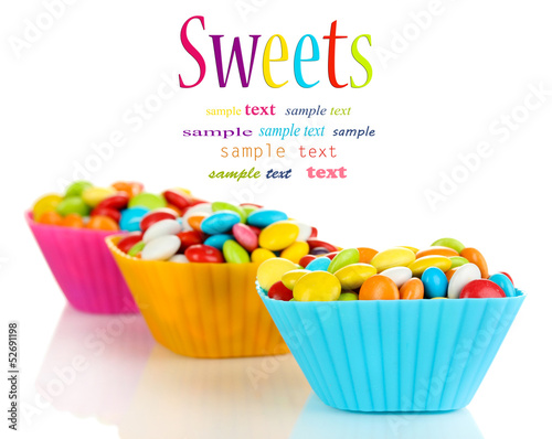 Colorful candies in cupcake cases isolated on white