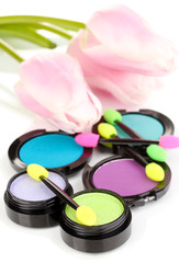 Bright eye shadows and sponge brushes for foundation close up