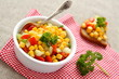 Homemade corn salsa in white bowl with spoon