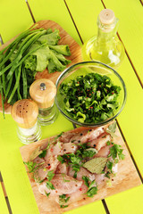 Chicken meat in glass plate,herbs and spices on wooden table