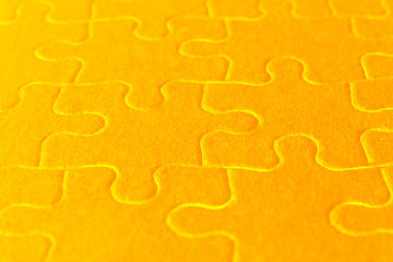 close up of orange jigsaw puzzle parts
