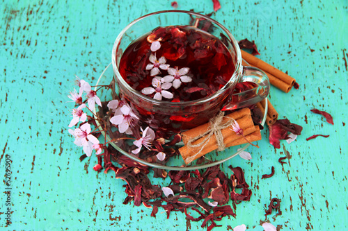 Herbal tea in glass cup, on color wooden background