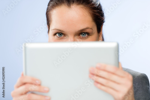 Woman holding digital tablet hiding her face