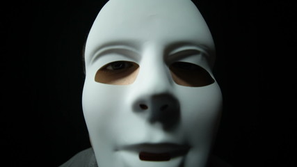 Scary masked man over dark background