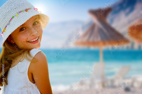 Lovely girl on tropical beach, beach chair and umbrella.
