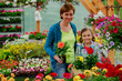 Mother with daughter shopping plants and flowers in garden cente