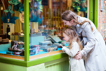 Mother and daughter looking at chocolate in shop