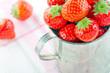 Strawberries in an old metal measurement cup