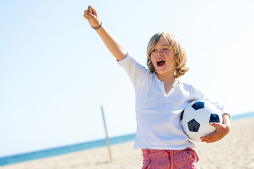 Boy with soccer ball and winning attitude.