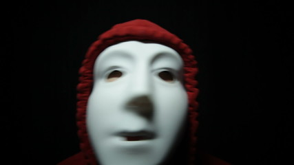 Creepy horror masked man over dark background
