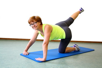 Mature, beautiful woman in yellow t-shirt practices yoga
