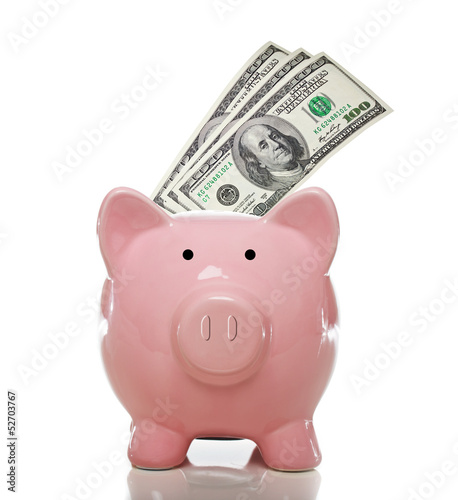 Pink piggy bank with hundred dollar bills