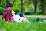 tender young couple relaxing on spring meadow poster