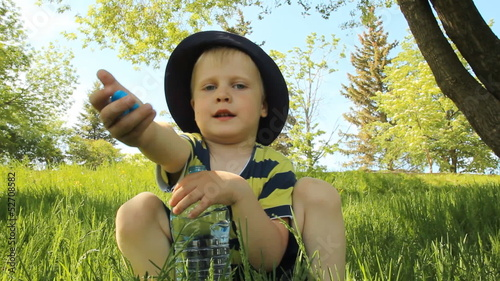 Little boy on the meadow drinking water from a clear plastic bot