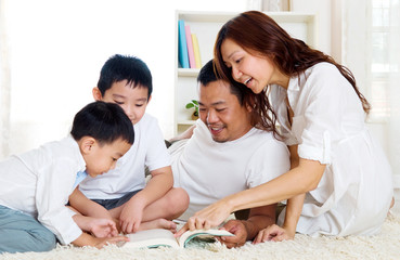 Asian family sharing a book