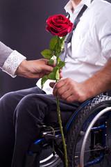 Rollstuhlfahrer übergibt eine Rose