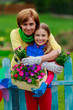 Gardening- lovely girl with mother working in flowers garden
