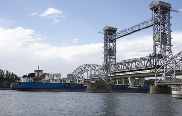 The ship floats under a drawbridge