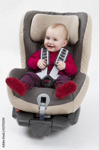 toddler in booster seat for a car in light background